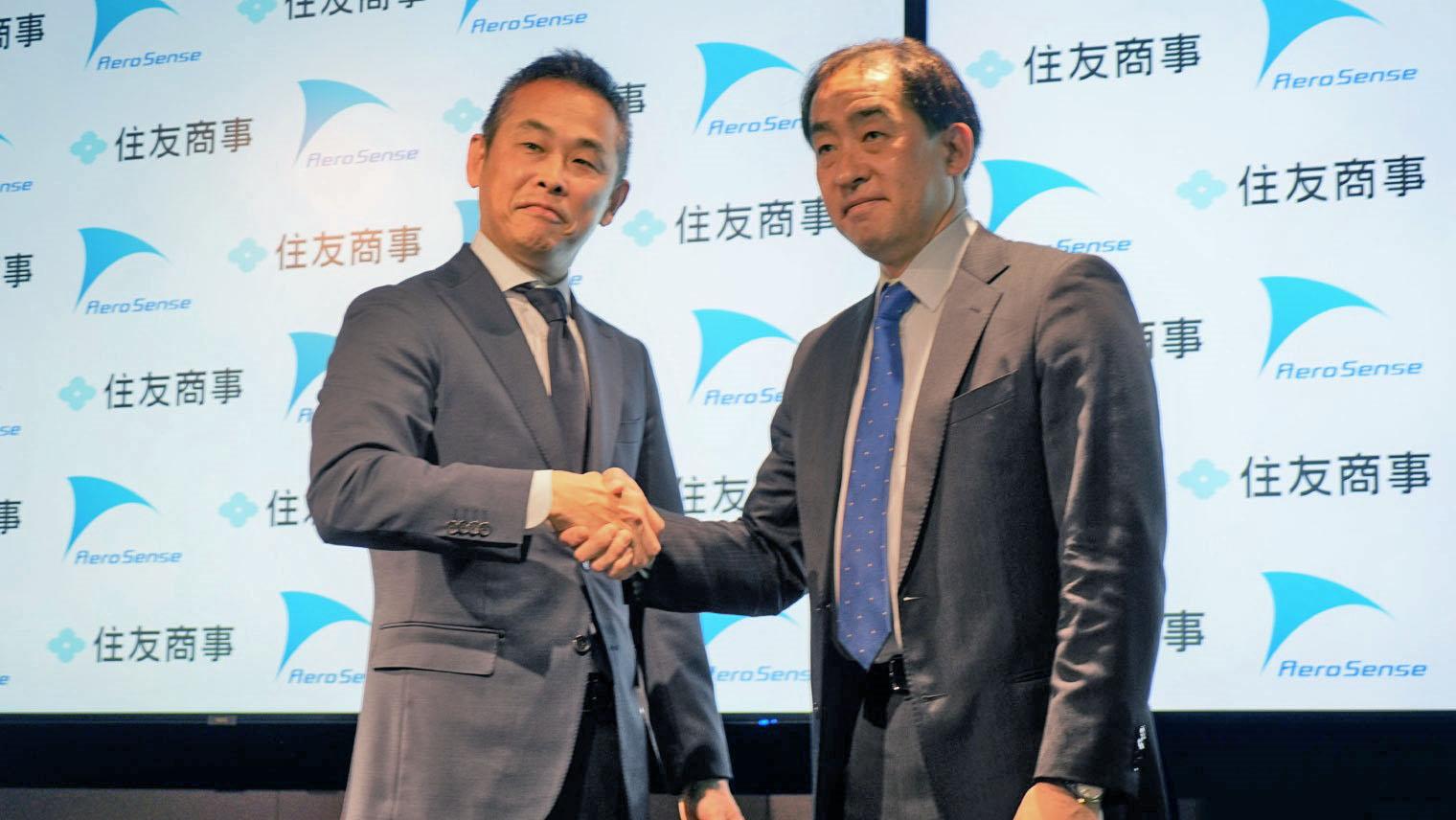 発表イベントにて、佐部さんと住友商事の人が握手をしている写真(2020年2月撮影)