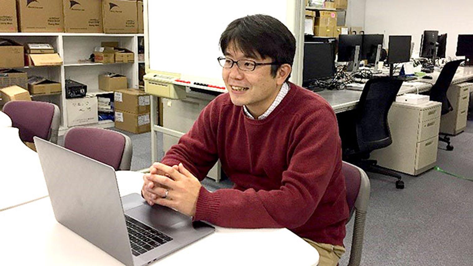 鈴木康輔さんがオフィスで話をしている写真