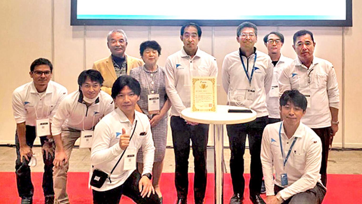 社員と協力者が表彰状を囲んで並んでいる写真