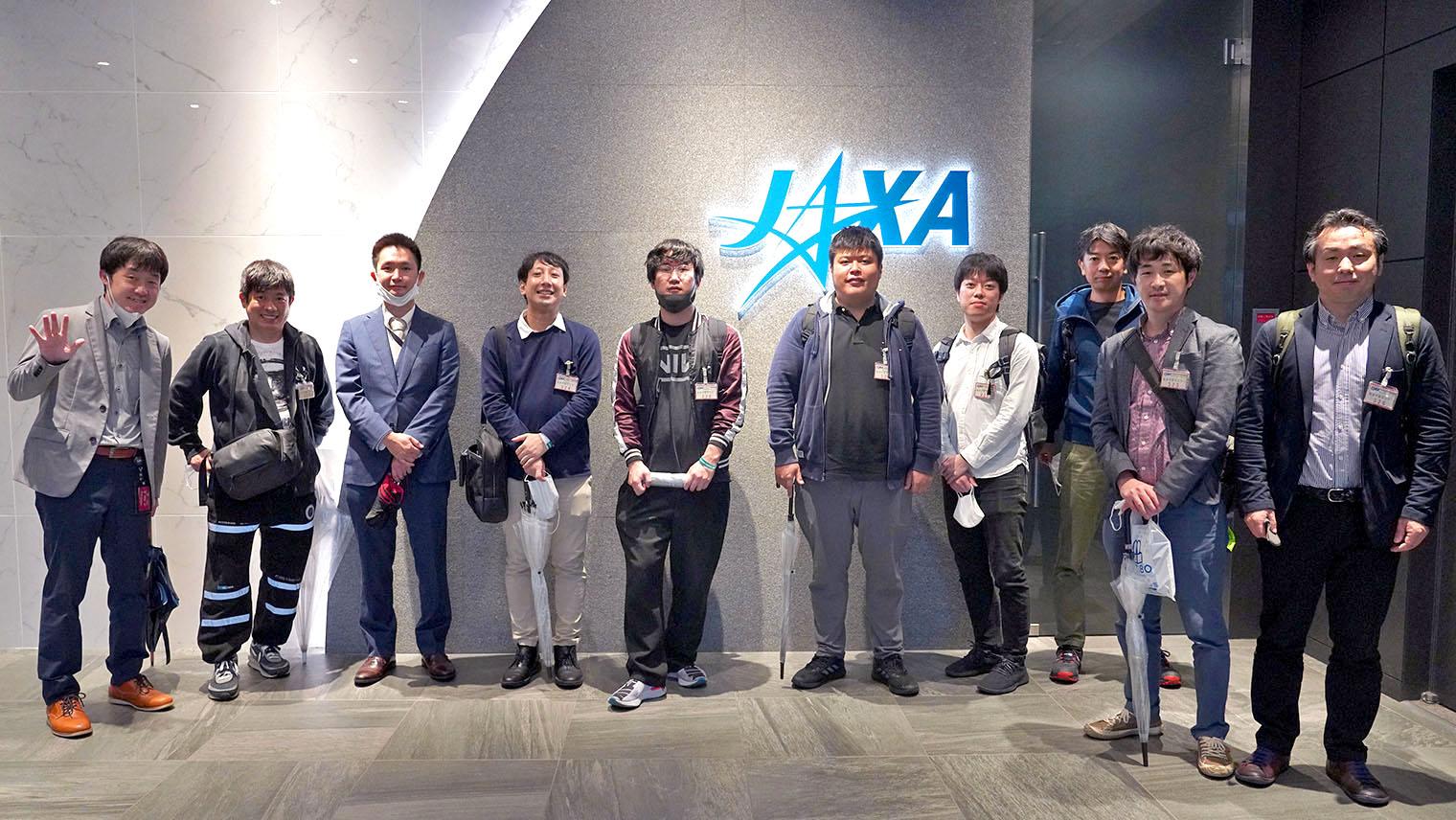 JAXAの施設内でプロジェクトメンバーの人たちが並んでいる写真