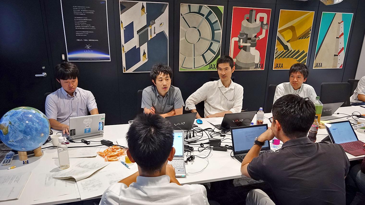 会議室の机の上にノートパソコンや資料を広げてプロジェクトメンバーが話し合っている写真