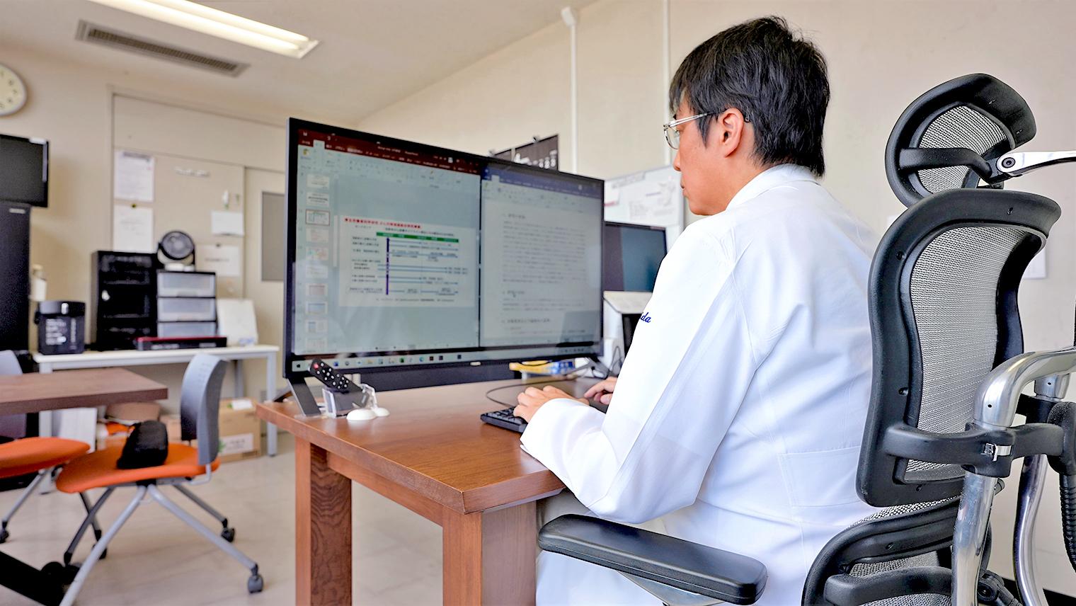 吉田先生が仕事場のパソコンで作業をしている写真