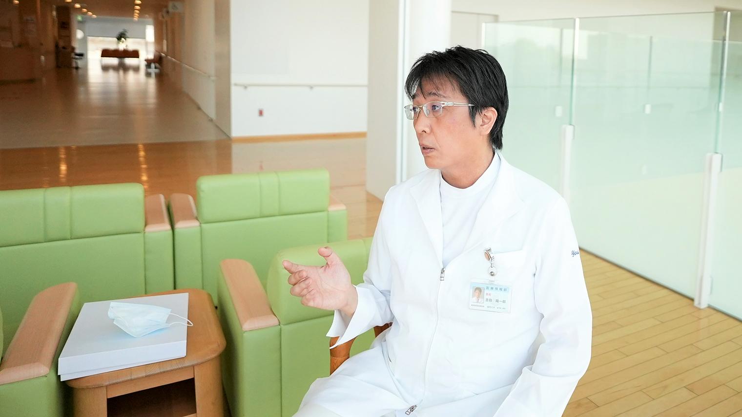 吉田先生がロビーでインタビューに応じている写真