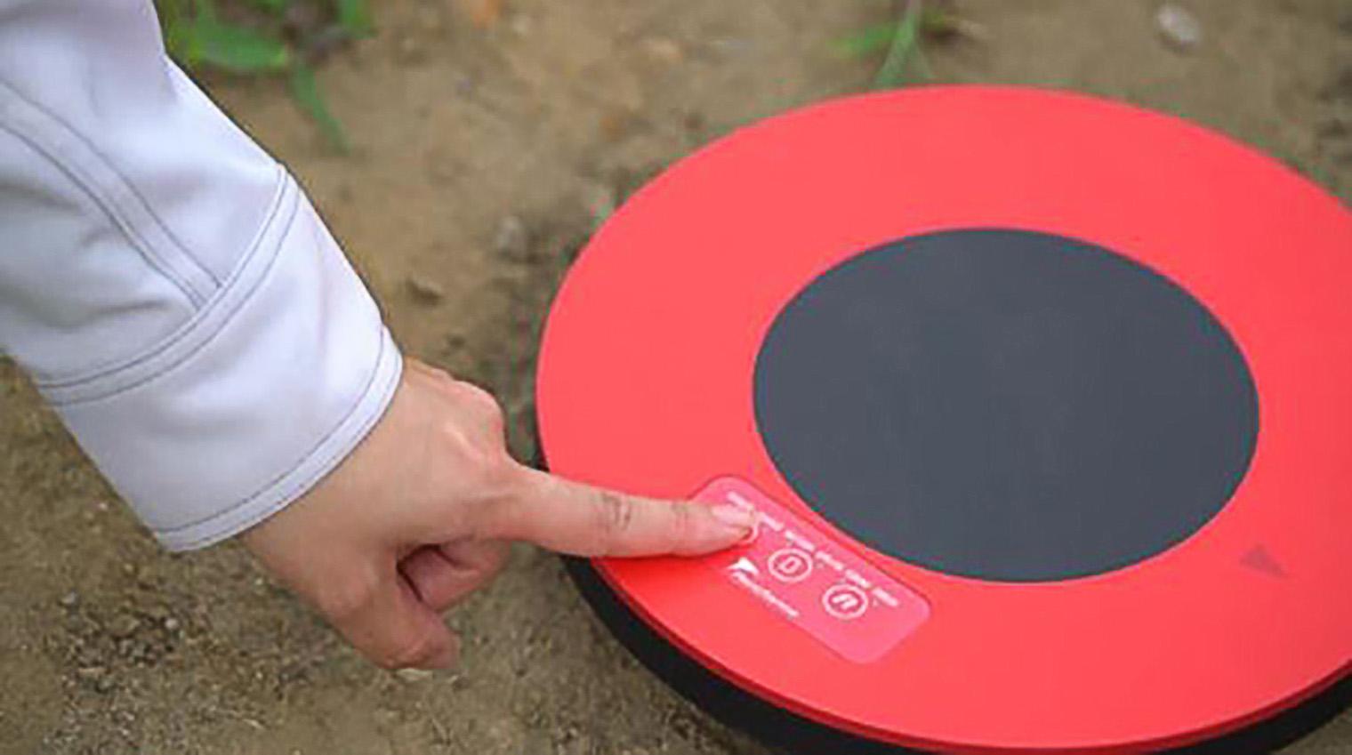 エアロボマーカーを地面に置きスイッチを押している写真