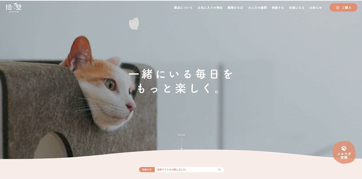猫壁公式サイトのトップページの画像、猫壁に乗る猫の写真と「一緒にいる毎日をもっと楽しく」というキャッチコピーが表示されている